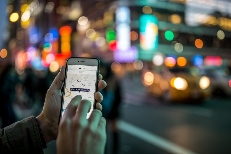 Man Using the Uber Taxi App on Iphone in NYC